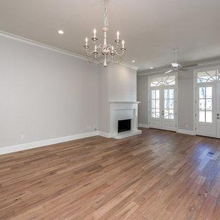 Foto de salón abierto, tradicional, de tamaño medio, con paredes marrones, suelo de madera clara, chimenea tradicional, marco de chimenea de ladrillo, televisor colgado en la pared y suelo beige