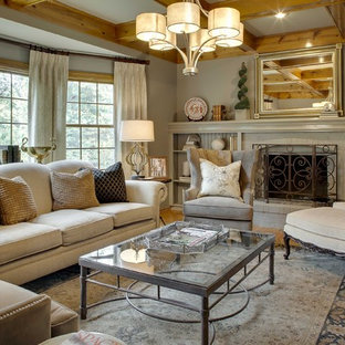 Exemple d'un salon chic de taille moyenne et fermé avec un mur gris, une cheminée standard, un manteau de cheminée en brique, un sol en bois clair, une salle de réception et aucun téléviseur.