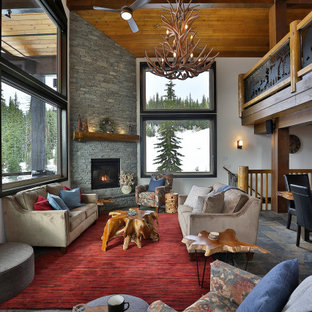 Rustikales Wohnzimmer im Loft-Stil mit weißer Wandfarbe, Schieferboden, Eckkamin, Kaminumrandung aus gestapelten Steinen, Wand-TV, grauem Boden und Holzdecke in Vancouver