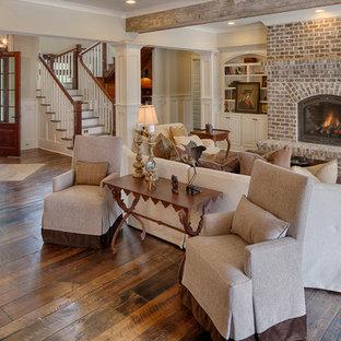 Idéer för att renovera ett stort vintage separat vardagsrum, med beige väggar, mellanmörkt trägolv, en standard öppen spis och en spiselkrans i tegelsten