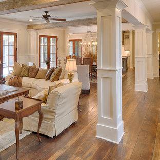 Foto di un grande soggiorno chic aperto con pareti beige, pavimento in legno massello medio, camino classico e cornice del camino in mattoni