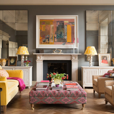 Transitional medium tone wood floor and brown floor living room photo in Edinburgh with gray walls and a standard fireplace