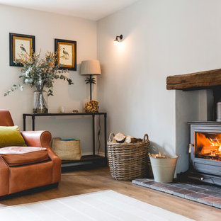 Photo of a country living room in London with white walls, medium hardwood flooring, a wood burning stove and brown floors.