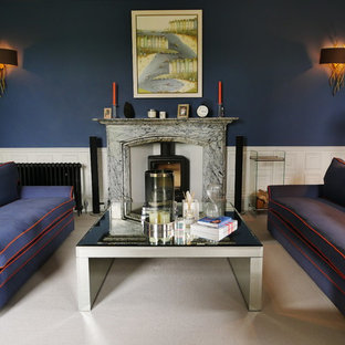 This is an example of a large traditional formal enclosed living room in West Midlands with blue walls, carpet, a wood stove, a stone fireplace surround, a wall-mounted tv and grey floor.