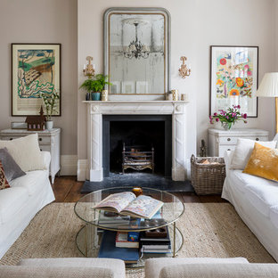 Inspiration for a traditional formal living room in London with grey walls, a stone fireplace surround, medium hardwood flooring, a standard fireplace, no tv and brown floors.