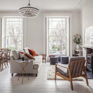 Modelo de salón clásico renovado, sin televisor, con paredes blancas, suelo de madera pintada y estufa de leña