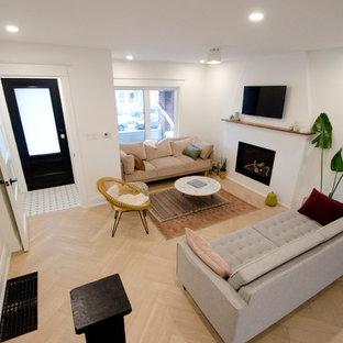 トロントの中サイズのコンテンポラリースタイルのおしゃれなLDK (白い壁、無垢フローリング、標準型暖炉、壁掛け型テレビ、ベージュの床、漆喰の暖炉まわり) の写真