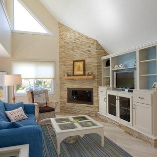 他の地域の中サイズのビーチスタイルのおしゃれなLDK (淡色無垢フローリング、コーナー設置型暖炉、石材の暖炉まわり、埋込式メディアウォール、ベージュの壁、黄色い床) の写真