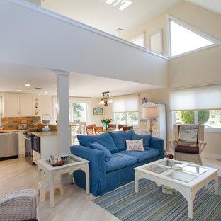 他の地域の中サイズのビーチスタイルのおしゃれなLDK (コーナー設置型暖炉、淡色無垢フローリング、石材の暖炉まわり、埋込式メディアウォール、ベージュの壁、白い床) の写真
