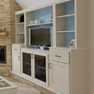他の地域の中サイズのビーチスタイルのおしゃれなLDK (淡色無垢フローリング、コーナー設置型暖炉、石材の暖炉まわり、埋込式メディアウォール、ベージュの壁、白い床) の写真