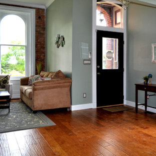 Design ideas for a small traditional formal enclosed living room in St Louis with green walls, medium hardwood floors, a hanging fireplace, a metal fireplace surround, a freestanding tv and beige floor.