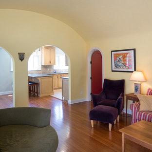 ロサンゼルスの中サイズの地中海スタイルのおしゃれなLDK (フォーマル、黄色い壁、無垢フローリング、標準型暖炉、漆喰の暖炉まわり、据え置き型テレビ) の写真