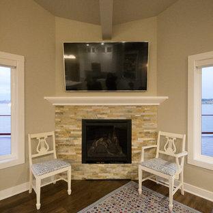 シアトルの小さいビーチスタイルのおしゃれなLDK (グレーの壁、クッションフロア、コーナー設置型暖炉、石材の暖炉まわり、壁掛け型テレビ) の写真