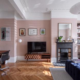Modelo de salón tradicional renovado, de tamaño medio, con paredes rosas, suelo de madera en tonos medios, chimenea tradicional, marco de chimenea de baldosas y/o azulejos, televisor colgado en la pared y suelo marrón