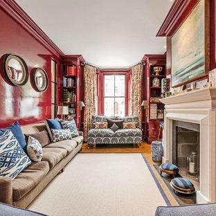 Ispirazione per un soggiorno tradizionale di medie dimensioni con pareti rosse, pavimento in legno massello medio, camino classico e libreria