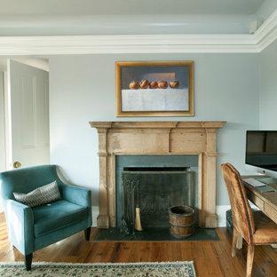 フィラデルフィアの大きいカントリー風おしゃれな独立型リビング (グレーの壁、標準型暖炉、木材の暖炉まわり、壁掛け型テレビ、無垢フローリング) の写真