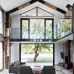 Imagen de salón abierto, urbano, de tamaño medio, con suelo de cemento, estufa de leña, televisor colgado en la pared, paredes blancas y suelo gris