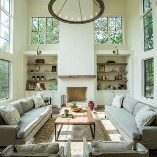 Diseño de salón de estilo de casa de campo con paredes blancas, suelo de madera en tonos medios, chimenea tradicional y suelo marrón