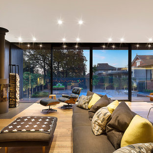 This is an example of a contemporary formal open plan living room in Melbourne with brown walls, medium hardwood flooring and a wood burning stove.