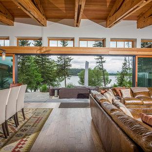 Ejemplo de salón abierto, rural, con paredes beige, suelo de madera en tonos medios, estufa de leña y marco de chimenea de piedra