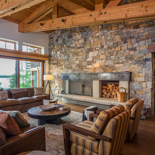 Mountain style open concept medium tone wood floor living room photo in Seattle with beige walls, a wood stove and a stone fireplace