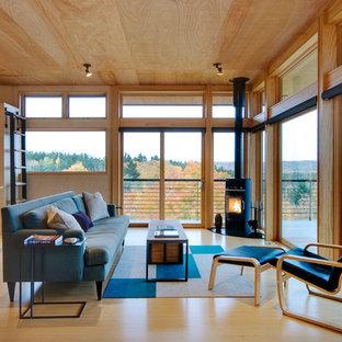 Imagen de salón para visitas abierto, actual, de tamaño medio, sin televisor, con estufa de leña, paredes beige, suelo de madera clara y marco de chimenea de metal