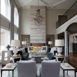 Idee per un grande soggiorno classico aperto con sala formale, pareti grigie, pavimento in legno massello medio, camino bifacciale, cornice del camino in pietra e nessuna TV