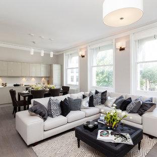 Esempio di un soggiorno minimal aperto con pareti beige e pavimento in legno massello medio
