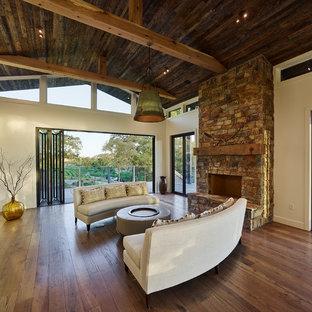 Foto de salón para visitas abierto, rústico, grande, sin televisor, con paredes blancas, suelo de madera en tonos medios, chimenea tradicional, marco de chimenea de piedra y suelo marrón