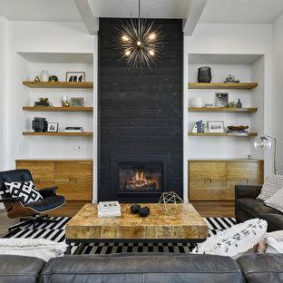 Fernseherloses, Offenes Klassisches Wohnzimmer mit weißer Wandfarbe, braunem Holzboden, Kamin, Kaminumrandung aus Holz, braunem Boden und freigelegten Dachbalken in Boise