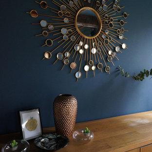 Foto di un soggiorno minimal di medie dimensioni e chiuso con pareti blu, parquet chiaro, cornice del camino in mattoni e TV autoportante