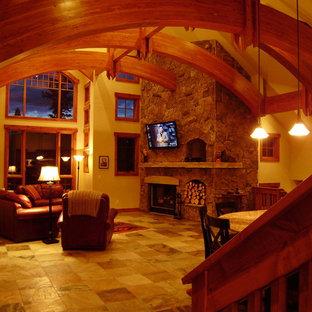 Esempio di un grande soggiorno rustico aperto con pavimento in ardesia, camino classico, cornice del camino in pietra, TV a parete, pavimento beige e pareti beige