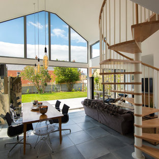 Photo of an expansive modern open plan living room in Buckinghamshire with white walls, a wall mounted tv and grey floors.