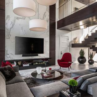 Cette photo montre un très grand salon tendance ouvert avec un mur multicolore, un téléviseur fixé au mur, un sol beige et un sol en carrelage de céramique.
