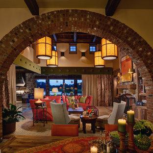 オーランドの中サイズの地中海スタイルのおしゃれなLDK (ベージュの壁、トラバーチンの床、標準型暖炉、木材の暖炉まわり、壁掛け型テレビ) の写真
