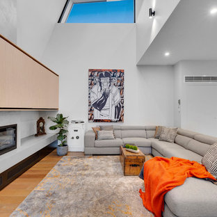 This is an example of a mid-sized contemporary open concept living room in Melbourne with white walls, a ribbon fireplace, a metal fireplace surround, medium hardwood floors, a concealed tv and brown floor.