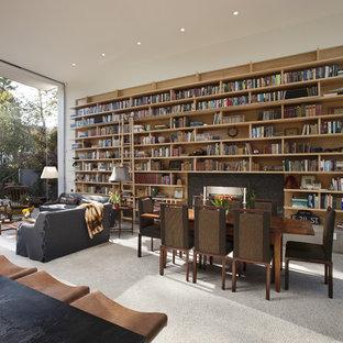 Immagine di un piccolo soggiorno moderno aperto con libreria, pareti bianche, pavimento in cemento, camino classico e cornice del camino in pietra