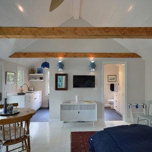Ejemplo de salón abierto, actual, pequeño, con paredes amarillas, suelo de madera pintada, estufa de leña y marco de chimenea de piedra