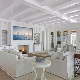 Imagen de salón con barra de bar abierto, marinero, grande, con paredes blancas, suelo de madera en tonos medios, chimenea tradicional, marco de chimenea de piedra, televisor colgado en la pared y suelo gris