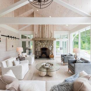 Idee per un grande soggiorno country aperto con sala formale, pareti beige, parquet chiaro, camino classico, cornice del camino in pietra, TV nascosta e pavimento beige