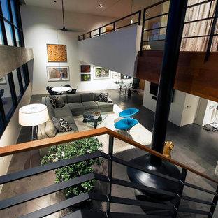 Foto di un ampio soggiorno moderno stile loft con pareti bianche, pavimento in cemento, camino sospeso, TV a parete e pavimento grigio