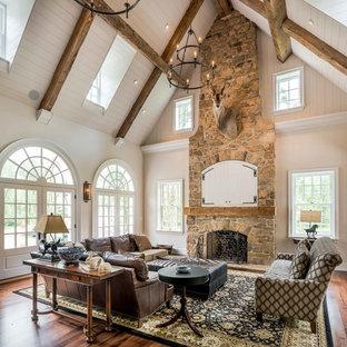 Idéer för stora rustika allrum med öppen planlösning, med vita väggar, mellanmörkt trägolv, en standard öppen spis, en spiselkrans i sten, en dold TV och brunt golv