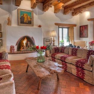 Großes, Fernseherloses, Abgetrenntes Mediterranes Wohnzimmer mit weißer Wandfarbe, Backsteinboden, Kamin und verputzter Kaminumrandung in Albuquerque