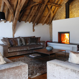 Inspiration for a large rustic mezzanine living room in Cornwall with white walls, concrete flooring, a wood burning stove, a stone fireplace surround and a wall mounted tv.
