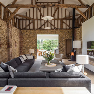 This is an example of a contemporary open plan living room in London with white walls, light hardwood flooring, a wall mounted tv, beige floors, exposed beams and a vaulted ceiling.