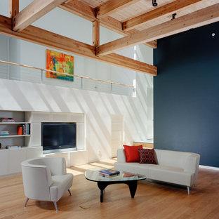 Ejemplo de salón abierto, moderno, de tamaño medio, con paredes azules, pared multimedia y suelo de madera clara