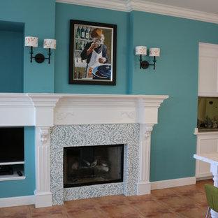 Неиссякаемый источник вдохновения для домашнего уюта: открытая гостиная комната среднего размера в морском стиле с синими стенами, полом из терракотовой плитки, стандартным камином, фасадом камина из плитки, мультимедийным центром и коричневым полом