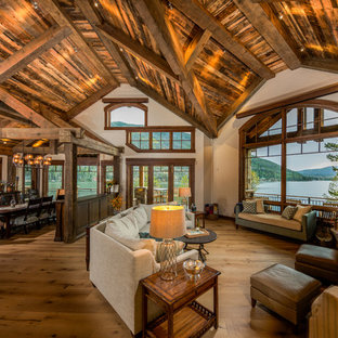 Living room - mid-sized rustic formal and open concept medium tone wood floor and brown floor living room idea in Denver with beige walls, a standard fireplace, a stone fireplace and a wall-mounted tv