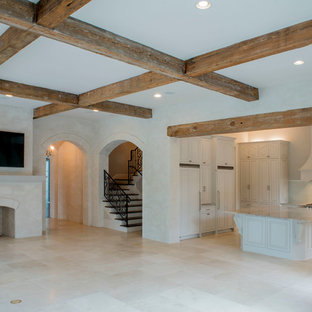 Huge country enclosed porcelain floor and beige floor living room photo in New Orleans with beige walls, a standard fireplace, a plaster fireplace and a wall-mounted tv