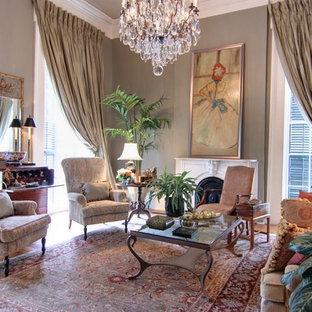 Imagen de salón para visitas abierto, tradicional, de tamaño medio, sin televisor, con paredes grises, suelo de madera oscura, chimenea tradicional y marco de chimenea de yeso